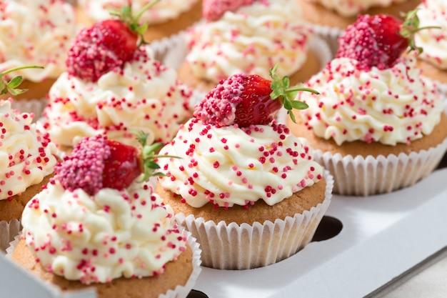 Cupcakes alla vaniglia decorato fragole fresche in scatola di consegna Foto Premium