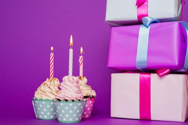 Cupcakes con candela accesa accanto a regali Foto Gratuite