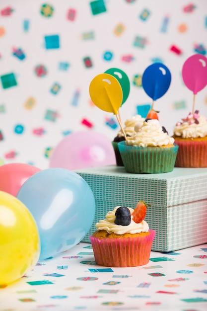 Cupcakes con toppers palloncino di carta sulla scatola Foto Gratuite