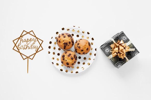 Cupcakes e presente di compleanno su fondo bianco Foto Gratuite