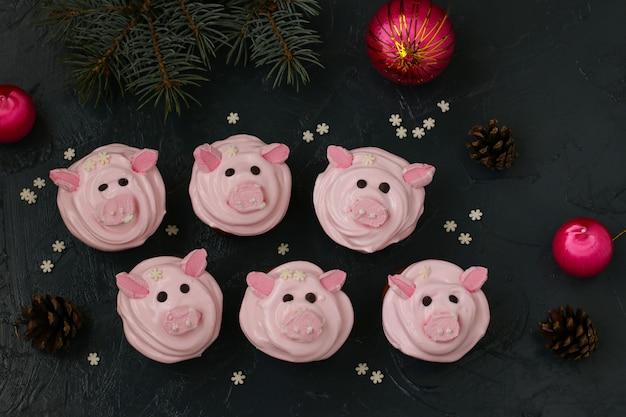 Cupcakes rosa fatti in casa decorati con crema proteica e divertenti maialini a forma di marshmallow Foto Premium