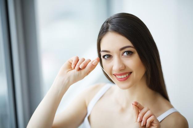 Cura dei denti. denti bianchi sani di filo interdentale sorridenti della bella donna. Foto Premium