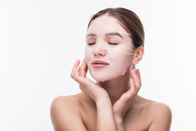 Cura del viso e trattamenti di bellezza. giovane donna con una maschera idratante del panno sul suo fronte isolato sulla parete grigia Foto Gratuite