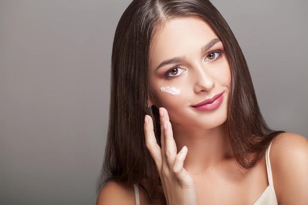 Cura della pelle . bella donna con crema per le mani, lozione per le mani. Foto Premium