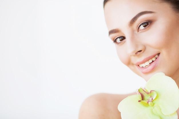 Cura della pelle. bellissima modella donna con pelle perfetta e fiore di orchidea vicino al viso Foto Premium
