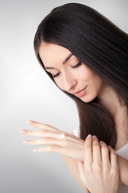 Cura della pelle di bellezza. bella donna che applica crema cosmetica per il viso Foto Premium