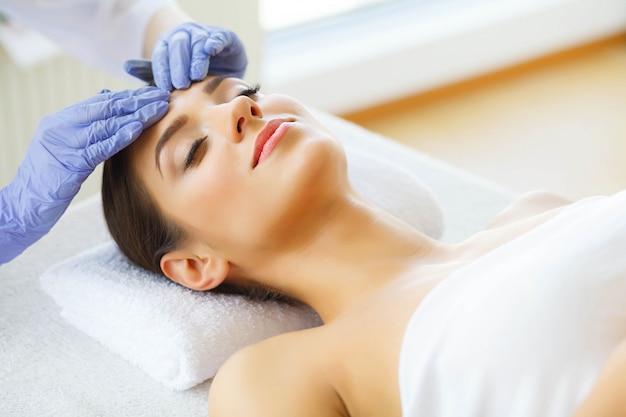 Cura della pelle procedure cutanee. bellissima giovane donna nel salone spa. sdraiato su lettini da massaggio e relax. alta risoluzione Foto Premium