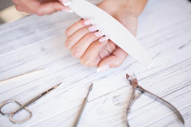 Cura delle mani della donna. primo piano di belle mani femminili che hanno manicure spa al salone di bellezza. chiodi naturali sani dell'archivista dei clienti dell'estetista con la lima per unghie. trattamento delle unghie Foto Premium