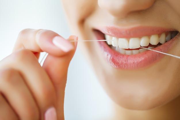 Cure odontoiatriche. donna con bel sorriso usando il filo per i denti. immagine Foto Premium