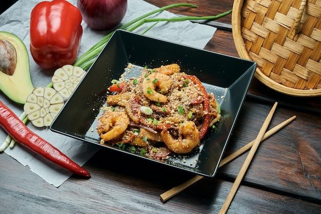 Cuscinetto tailandese o phad tailandese - tagliatelle di riso fritte wok di un piatto tailandese classico con i gamberetti e le verdure in una banda nera su una tavola di legno. avvicinamento Foto Premium