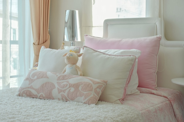 Cuscini rosa e beige sul letto accanto alla finestra Foto Premium
