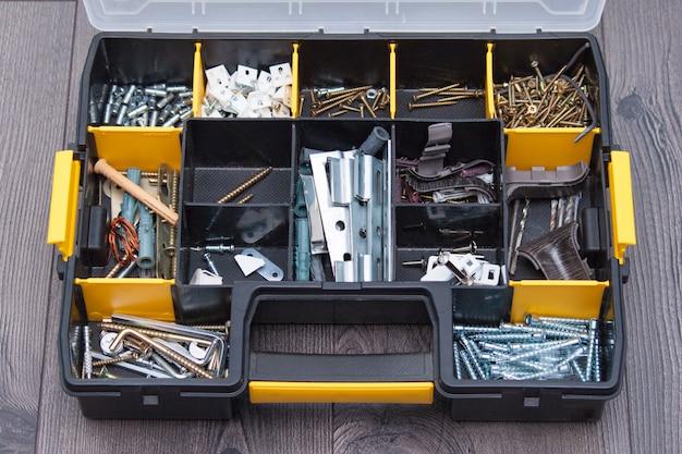 Custodia in plastica con elementi hardware, primo piano. scatola con chiodi, viti, bulloni, tasselli. Foto Premium