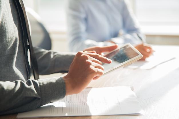 D'affari che lavora con tavoletta digitale in ufficio Foto Gratuite