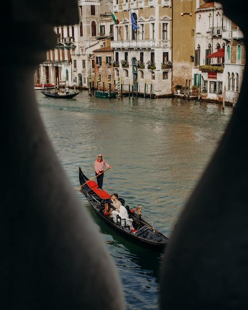 Da una vista del ponte sulla bella coppia durante un giro sul canale Foto Gratuite