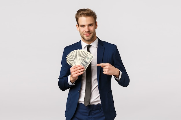 Dai un'occhiata a come appare il successo. l'uomo d'affari bello con incassa le mani, indicando i soldi e sorridendo sicuro, vantandosi, discute su come gestire gli affari, avviando la propria azienda Foto Premium