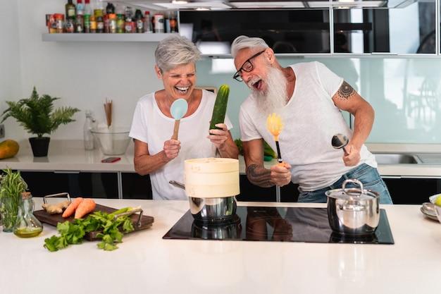 Dancing senior felice delle coppie mentre cucinando insieme a casa Foto Premium