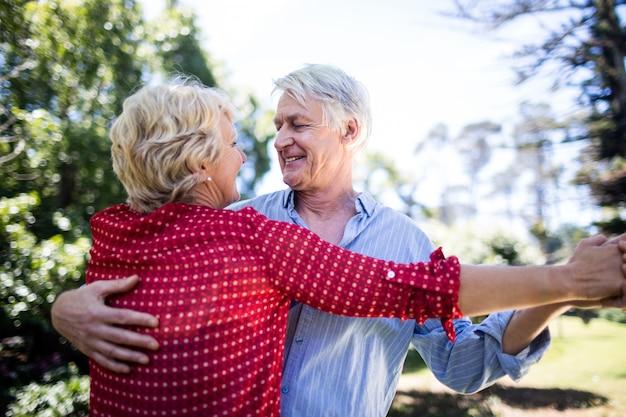 Dancing senior felice delle coppie nel parco Foto Premium