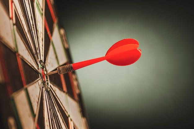 Dardo rosso nel centro dell'occhio di tori di un bersaglio Foto Premium