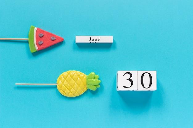 Data del calendario 30 giugno e frutta estiva caramelle ananas, lecca lecca cocomero. Foto Premium