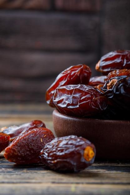 Date dolci in un piatto dell'argilla sulle mattonelle di pietra e sul fondo di legno, primo piano. Foto Gratuite