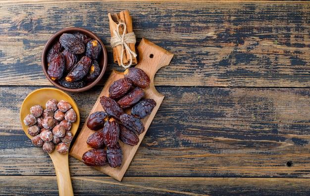 Date fresche in ciotola e tagliere con le noci nella vista superiore dei bastoncini di cannella e del cucchiaio di legno su fondo di legno Foto Gratuite