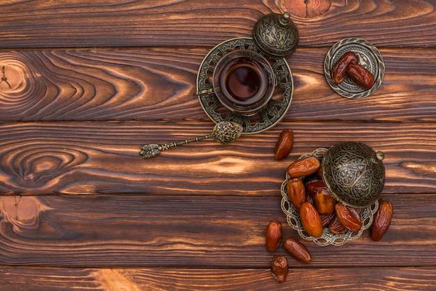 Date frutta con una tazza di tè sul tavolo Foto Gratuite