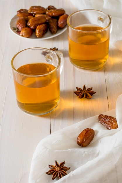Date frutta sul piatto con tazze da tè Foto Gratuite