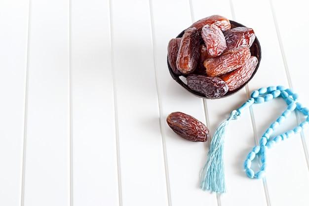 Date organiche isolate medjul e rosario blu in ciotola della noce di cocco su fondo bianco. Foto Premium