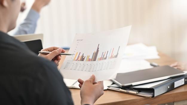 Dati di finanza statica di analisi dell'uomo d'affari del primo piano nella sala riunioni. Foto Premium