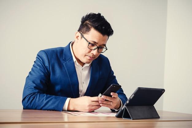 Dati serching dell'uomo d'affari con lo smartphone fra la riunione del brainstorming corporativo di successo Foto Premium