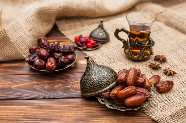 Datteri secchi e kumquat su piattini vicino a una tazza di tè tra il materiale di tela Foto Gratuite