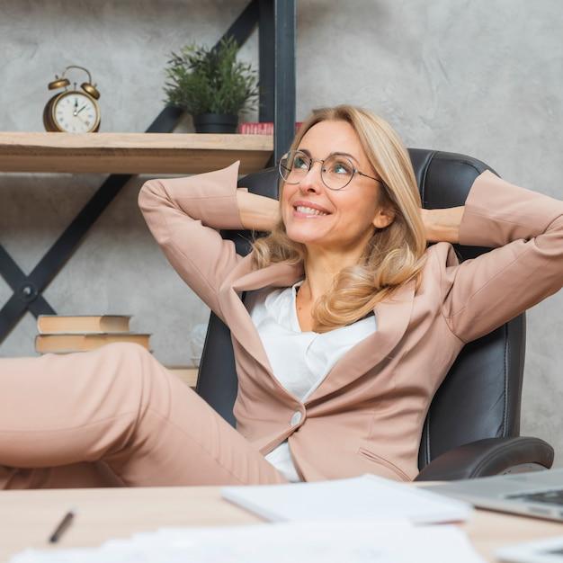 Daydreaming giovane imprenditrice rilassante sulla sedia in ufficio Foto Gratuite