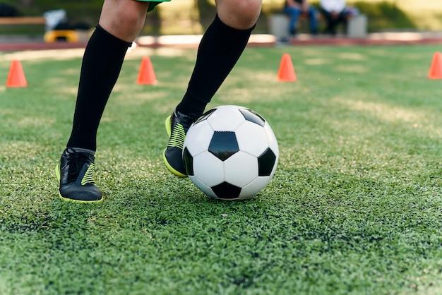 De close up di gambe e piedi del calciatore su erba verde Foto Premium