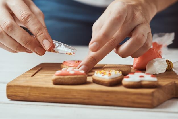 Decorare i biscotti di pan di zenzero con glassa. le mani della donna decorano i biscotti nella forma di cuore, primo piano Foto Premium