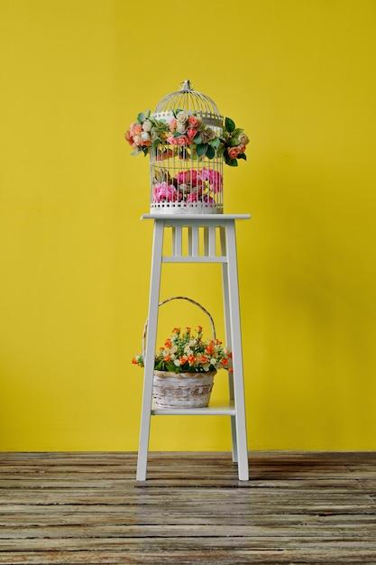 Decorazione della stanza con gabbia per uccelli e cestino con i fiori Foto Premium
