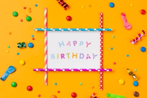 Decorazione di buon compleanno con streamer; palloncino; gemme e granelli su sfondo giallo Foto Gratuite