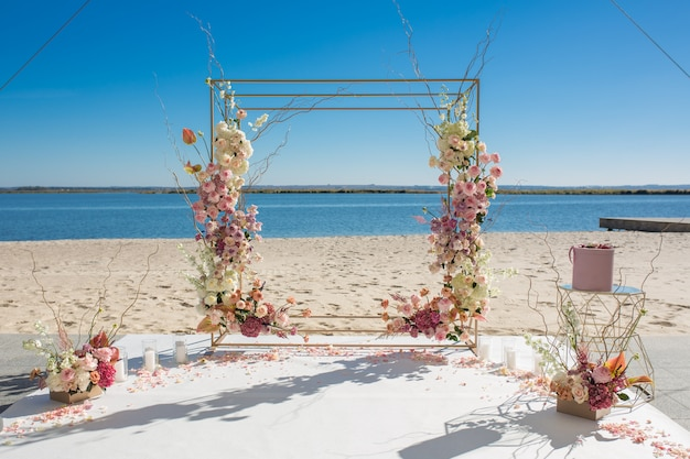 Decorazione di eventi chuppa di nozze in riva al fiume decorata con fiori freschi Foto Premium