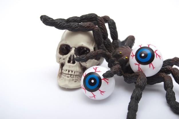 Decorazione di halloween, teschio con una tarantola in cima e due occhi, isolato Foto Premium