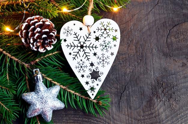 Decorazione di natale con abete, ghirlanda leggera e cuore bianco su legno vecchio Foto Premium