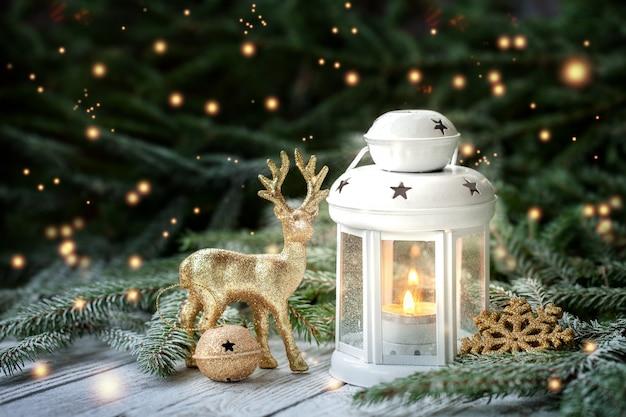 Decorazione di natale con lanterna, fiocco di neve d'oro e palle, rami di abete e ornamenti su sfondo scuro. Foto Premium