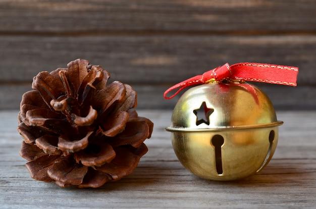 Decorazione di natale con pigna e campana di natale d'oro Foto Premium