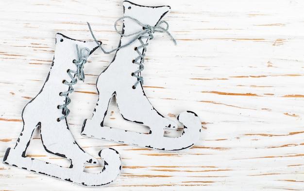 Decorazione di natale - pattini di legno su una vecchia tabella bianca. nuovo anno Foto Premium