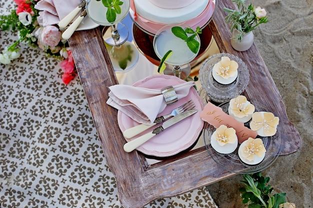 Decorazione di nozze, tavola decorata, candela, torta, belle stoviglie, colore nero, dorato e rosato Foto Premium