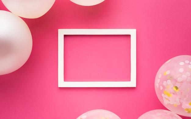 Decorazione piatta laica con palloncini, cornice e sfondo rosa Foto Gratuite