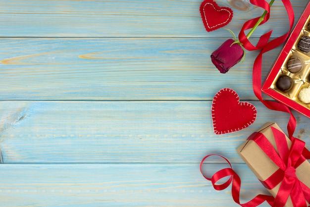 Decorazione romantica di giorno di san valentino con rose e cioccolato su un tavolo di legno blu. Foto Premium
