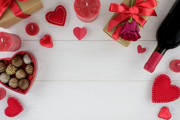 Decorazione romantica di giorno di san valentino con rose, vino e cioccolato su un tavolo di legno bianco. Foto Premium