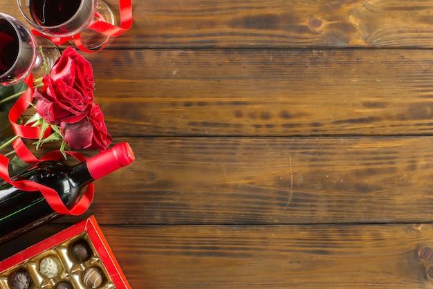 Decorazione romantica di san valentino con rose, vino e cioccolato su un tavolo in legno marrone Foto Premium