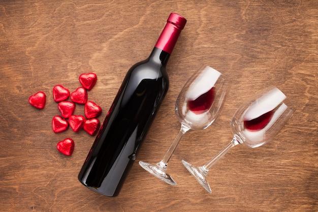 Decorazione vista dall'alto con caramelle a forma di cuore e vino Foto Gratuite