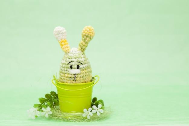 Decorazioni a maglia di uova di pasqua, fiori, coniglietto su uno sfondo verde, amigurumi Foto Premium