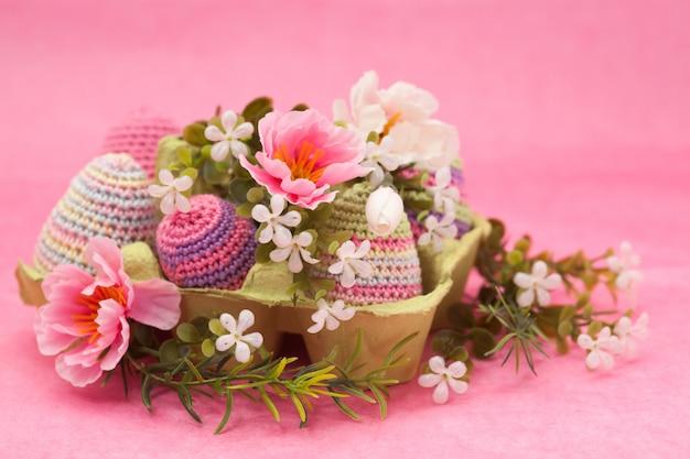 Decorazioni a maglia uova di pasqua, fiori su uno sfondo rosa, fatti a mano Foto Premium